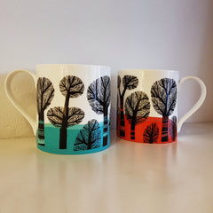 Two bone china mugs with tree designs in orange, turqouise and black