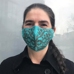 Turquoise face covering with fancy olive green pattern worn by woman with long dark hair in a plait