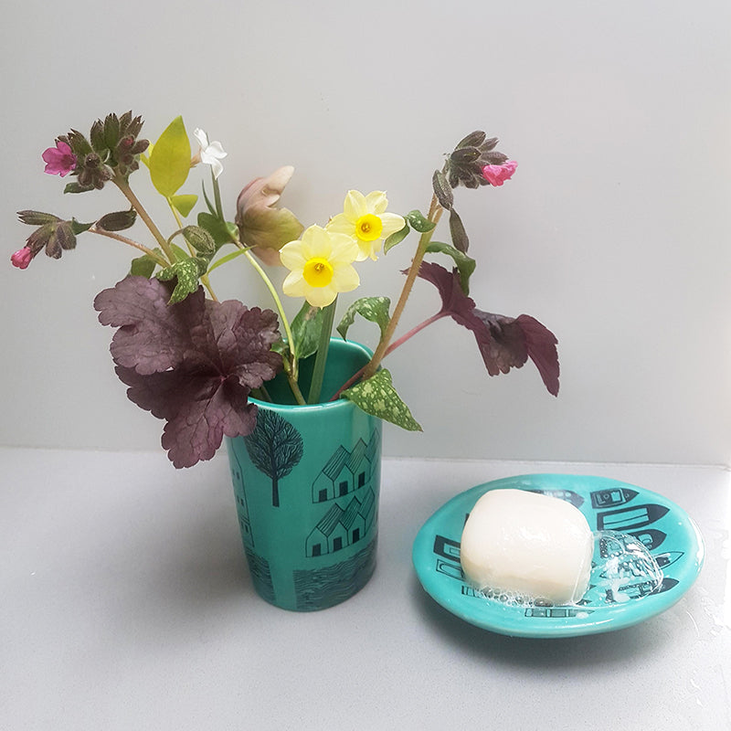 Lush Designs turquoise ceramic beaker with spring flowers in it, and soap dish with frothing soap