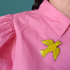 Lush designs yellow bird-shaped badge pin worn on a strawberry pink blouse