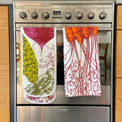 vegetable print oven gloves and carrot print tea towel hanging on an oven door