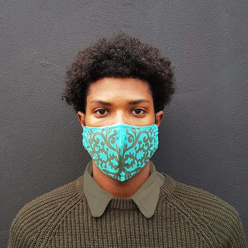 young man wearing turquoise and green patterned face mask