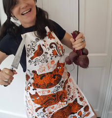 woman wearing cat print apron with big kitchen knife and beetroot