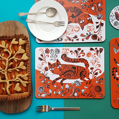 Tablw set with orange and black and white printed cat design mats and a fancy fruit pie