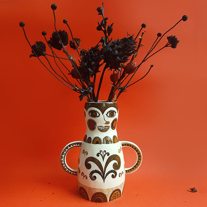 Lush Designs woman-shaped vase with black flower arrangement