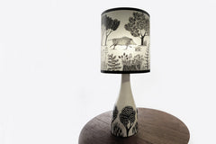 Lush Designs cream ceramic lamp base with black pattern of plants shown with wild boar print shade