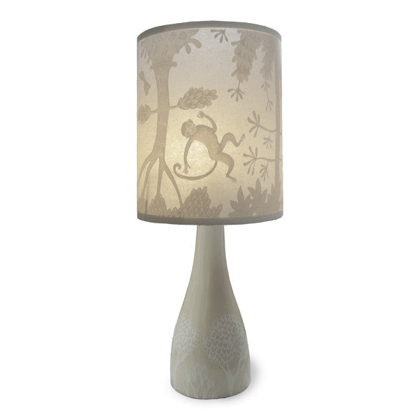Lush Designs ceramic lamp base in cream with subtle print in white shown with translucent shade with cream monkey print