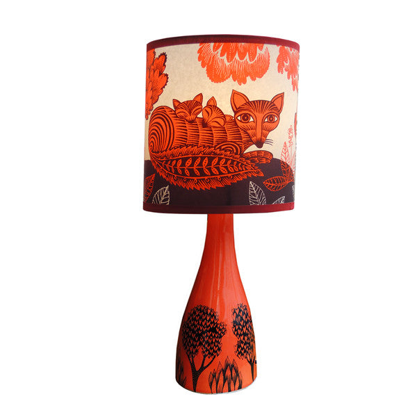 Lush designs small ceramic shade with orange red glaze printed with plants and trees in black shown with orange fox print lamp shade