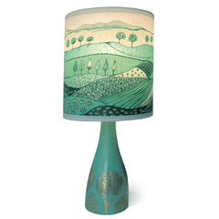Lush Designs jade ceramic lamp base with gold lustre print shown with green landscape print lamp shade