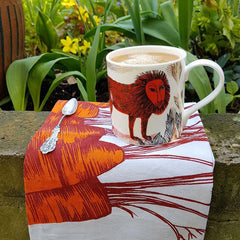 Lion mug photographed in the garden with a carrot printed tea towel
