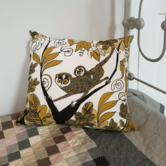 Lush designs cushion with print of slender loris on a bed with a grey patchwork quilt