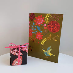 Lush designs greetings card with picture of singing bird and flowers next to a tiny gift-wrapped box