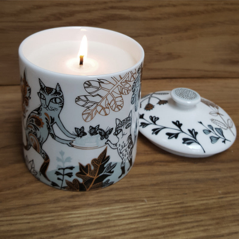 Bone china pot with lid decorated with pussy cat design in pale blue, black and gold, contains scented candle