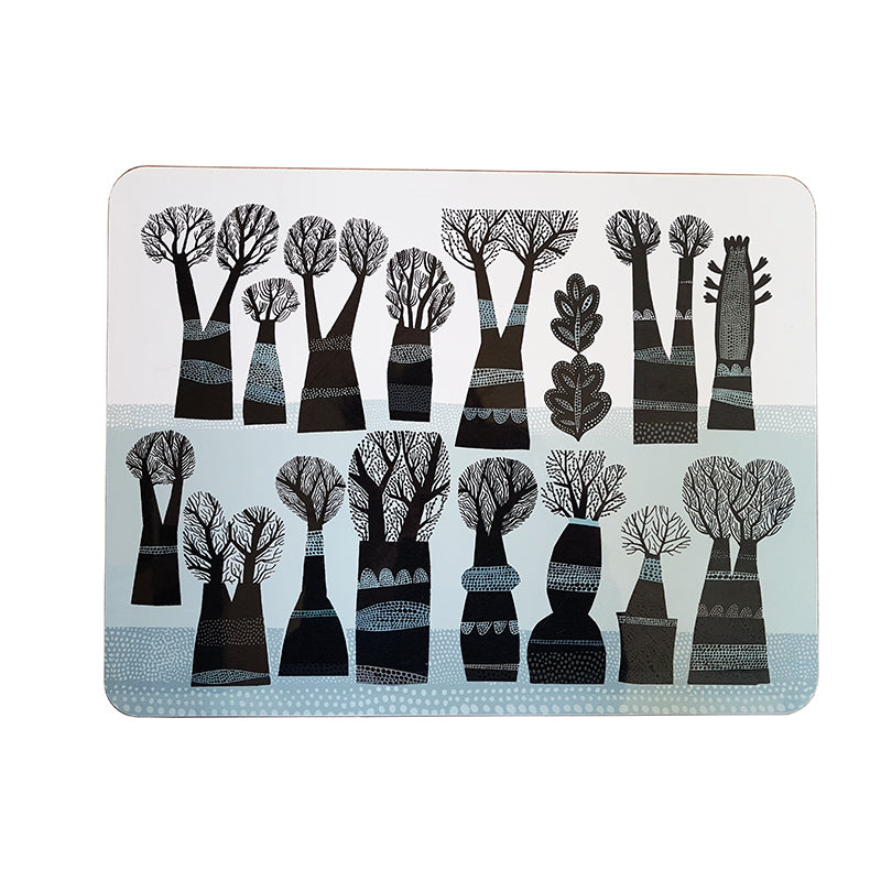 Lush Designs table mat with a design of black winter trees on a pale blue and white background