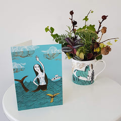 Mermaid birthday card next to a unicorn mug containing an autumn posy