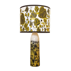 Lush Designs lampshade with detailed print of bushes, plants and gardening tools on a lamp base printed with a triangle pattern