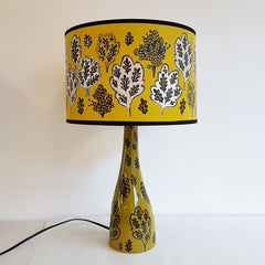 Ceramic lamp base with wide shade in mustard and olive green, printed with pattern of oak leaves and small trees