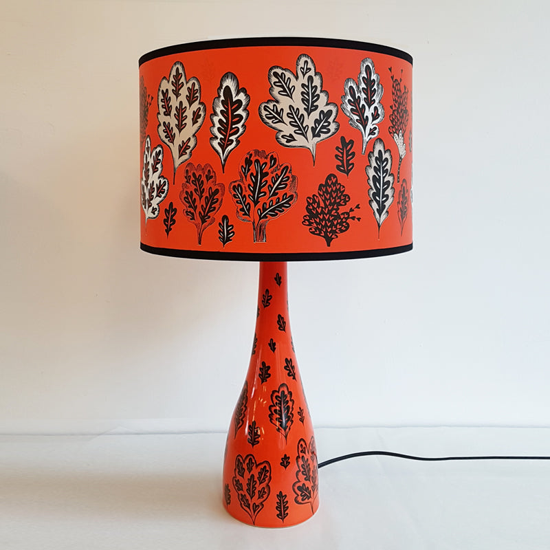Lush Designs lamp in red-orange decorated with oak leaves and trees.