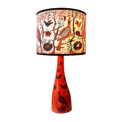 Bird print lamp shade in orange and black shown on orange ceramic bird printed lamp base