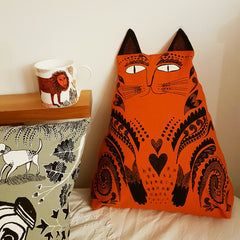 Lush Designs cat-shaped cushion in rich orange pictured on a sofa next to a lion-print cup