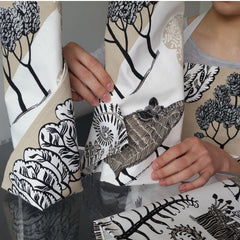 Wild boar napkins being folded by someone in a wild boar print apron