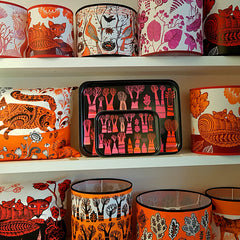 Shelves with Lampshades, trays and cushions are printed with illustrative designs in pink, orange, red and black