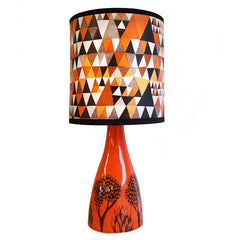 Lush Designs orange ceramic lamp base with black tree print shown with triangle patterned orangl, black and white shade
