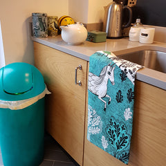 Lush Designs Unicorn print tea towel hanging over the edge of kitchen sink with oak doors and a tea coloured bin