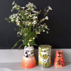 Orange kitty jar pictured with siskin bird-printed storage tin and orange and black patterned vase of daisies