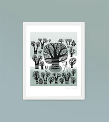 framed print of winter trees in a greyish green landscape against a soft teal wall