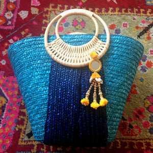 blue and yellow pom pom bag