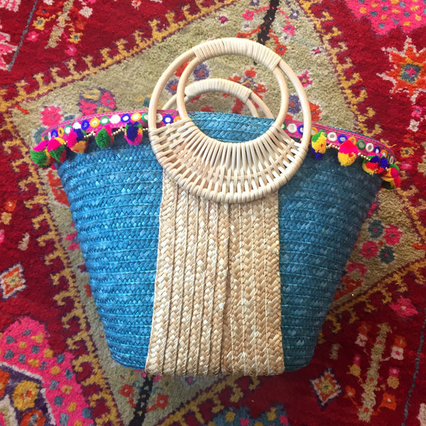 turquoise and beige bag with pom poms