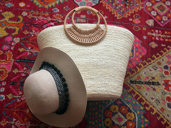white bag with black pom pom beige hat