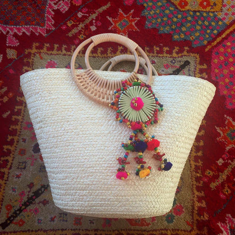 white beach bag with large colorful tassel
