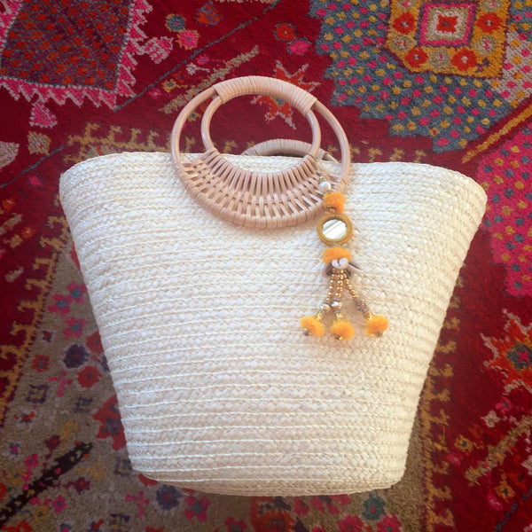 white beach bag with yellow tassel