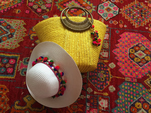 yellow beach bag with white pom pom hat