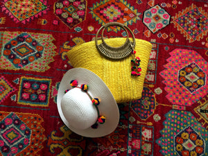yellow pom pom bag with white pom pom hat