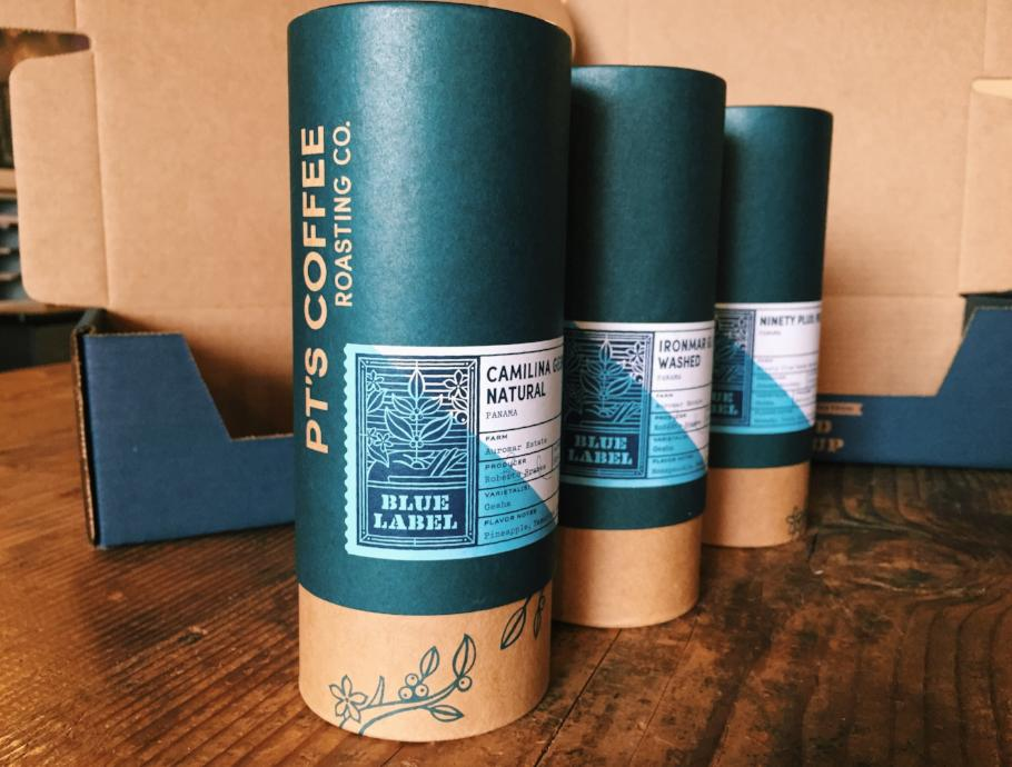 Three PT's Coffee Blue Label tubes standing on table.
