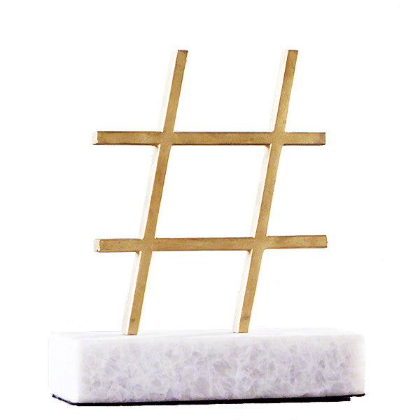 Gold leaf cast iron hashtag on a marble stand is at once elegant and humorous.