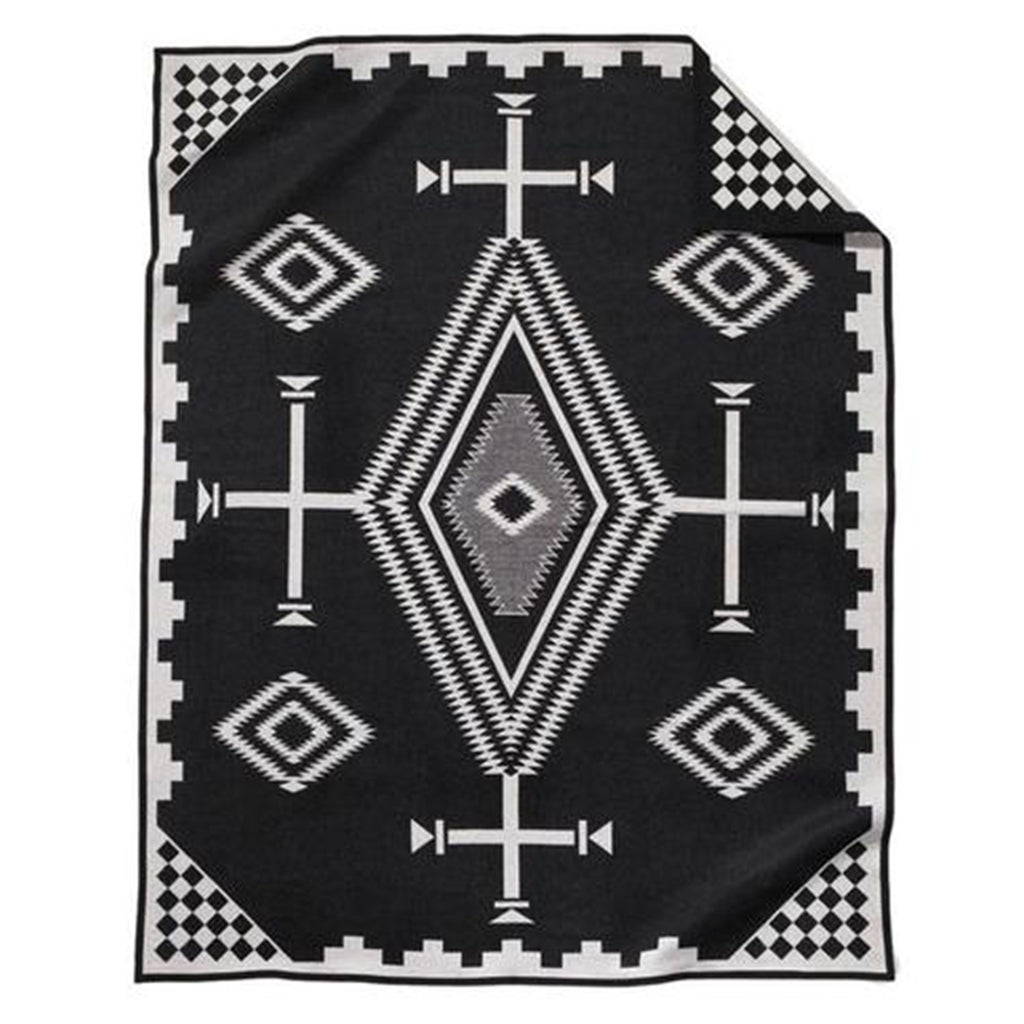 "Pendleton blankets are heirloom-quality wool blankets made in the USA using wool that sourced from ranches around the country. This reversible black twin los ojos blanket is modern and historic as it features Spanish crosses, diamond-shaped ""eyes"" (ojos) and the symbols of the Navajo Four Mountains of Creation."