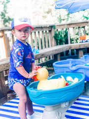 boy in rashguard, swim diaper, and hat playing at a water table