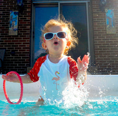 girl with pool toy and sunglasses
