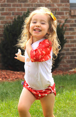 girl running on grass with a rashguard and swim diaper on