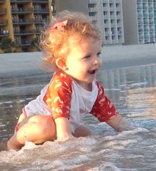 baby girl playing in the waves at the beach in a swim diaper and rashguard