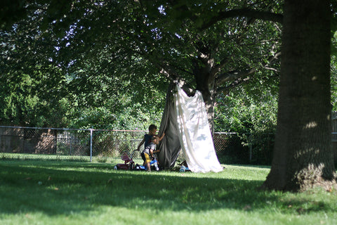 Two children playing in a blanket tent made under a tree.