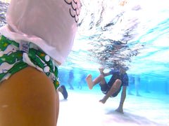 narwahl swim diaper underwater and brother in the water in the background wearing shark rash guard Beau and Belle Littles