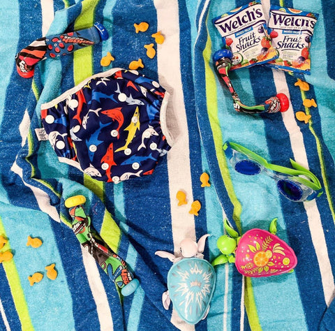 Two turtle toys, fruit snacks, shark print Beau and Belle Littles Swim diaper, and goggles laid out on a beach towel.