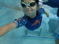 beau swimming underwater at Great Wolf Lodge wearing the BBLittles rash guard