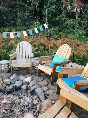 Four wooden arm chairs positioned around a fire pit.