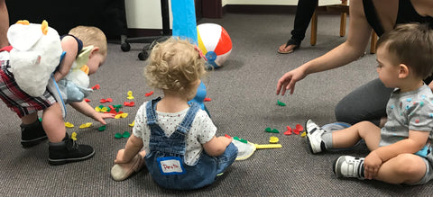 toddlers sitting on the floor playing with toys at the library